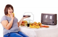 14092469-overweight-woman-eating-fast-food-and-watching-tv-isolated